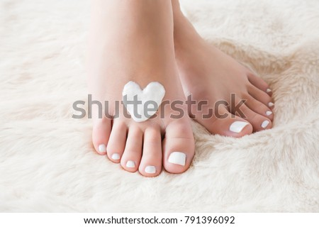 Elegant bare feet. Beautiful groomed woman's feet on the fluffy mat. Cares about clean and soft legs skin in winter time. Heart shape created from cream. Love a body. Healthcare concept. #791396092