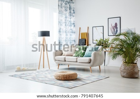 Black lamp standing by a sofa and a row of candles lying on the floor in front of a window shedding light on the interior of boho style living room Royalty-Free Stock Photo #791407645