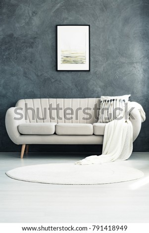 White circular rug lying in front of a comfortable beige sofa with a pillow and a blanket #791418949