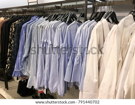 female colorful clothing set of on the racks in clothing store    #791440702