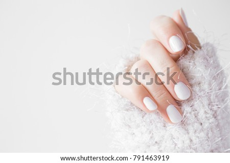 Beautiful groomed woman's hands with white nails on the light gray background. Nail varnishing in white color. Manicure, pedicure beauty salon concept. Empty place for text or logo.  #791463919