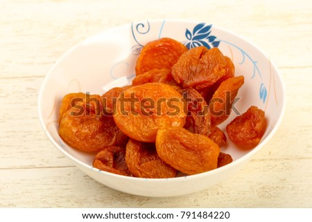 Dried apricots heap in the bowl over wooden background #791484220