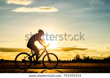 Silhouette man cycling in public park for healthy at sunset background #791491414