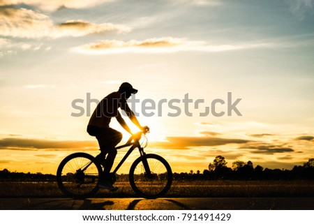 Silhouette man cycling in public park for healthy at sunset background #791491429