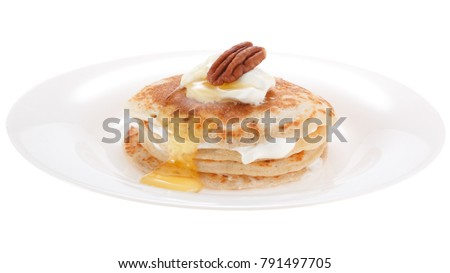 Serving pancakes with sour cream honey and nut on the plate. Isolated on white background. #791497705