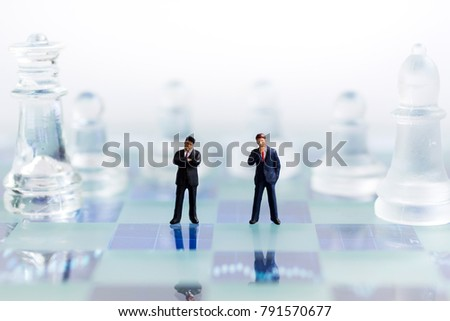 Miniature people, Businessmen stand on opposite sides of the chess game, separate party , benefit, use as a business competition concept. #791570677