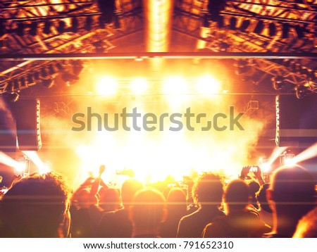 Flaming concert stage with crowd raising hands #791652310