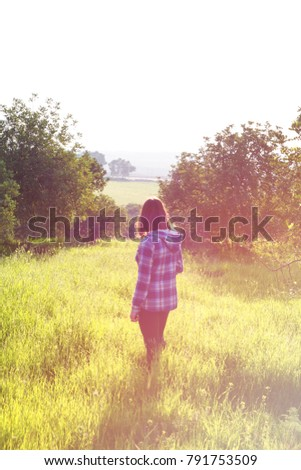 The concept of enjoying nature. Rest on the air. Girl in a hooded shirt #791753509