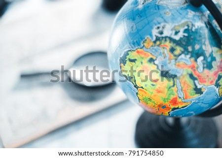 Map of roads with a magnifier on the background of the globe