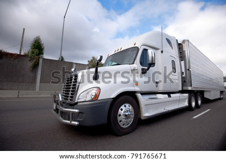 White modern American bonnet popular big rig semi truck for long haul delivery with reefer unit on refrigerator semi trailer running on the highway with concrete fence and cloudy sky #791765671