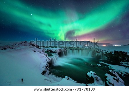 A stunning glowing aurora shape like phoenix bird appears above the landscape of Godafoss waterfall in winter Iceland