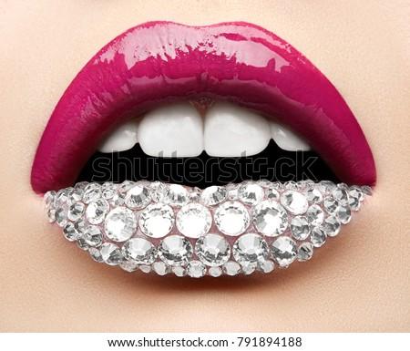 Macro and close-up creative make-up theme: beautiful female lips with pink lipstick, white diamonds and teeth, retouched photo #791894188