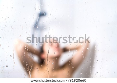 Young beautiful woman in shower. Behind wet glass window with water drops. Focus on droplets. Girl bathing, washing hair and taking fresh bath. #791920660
