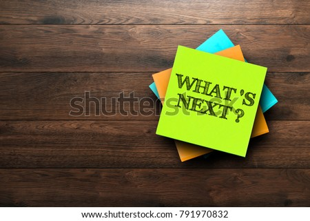What's next , the phrase is written on multi-colored stickers, on a brown wooden background. Business concept, strategy, plan, planning. #791970832