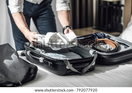 Hands of unrecognisable businessman packing his shirts in suitcase for business travel. Royalty-Free Stock Photo #792077920