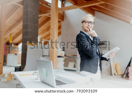 young, pretty, blonde architect is planning on the notebook and tablet the expansion of a loft #792093109