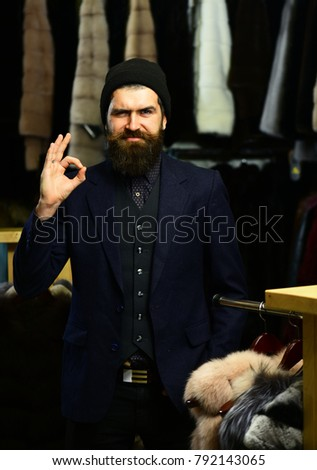 Fashion and shopping concept. Man with smiling face near furry coats on racks on background. Customer with beard and hat on. Businessman shows ok sign #792143065