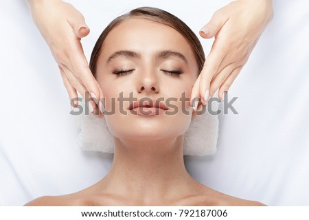 Cute  young girl with thick eyebrows and perfect skin doing facial massage, closed eyes, relaxing, beauty photo concept, stress free. #792187006