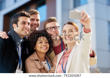 business, education and corporate concept - international group of people with conference badges and smartphone taking selfie on city street #792205087