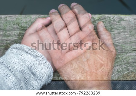 Semi-transparent man's hand on a woman's hand as a sign of farewell by separation or death Royalty-Free Stock Photo #792263239