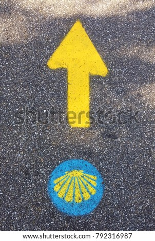 Traditional yellow arrow and symbol of the seashells painted on the way. Directional sign for pilgrims in Saint James way. Camino de Santiago de Compostela. #792316987