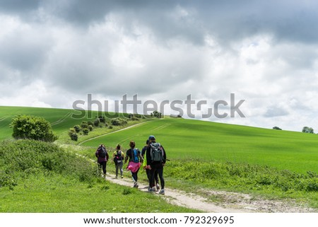 Group walking the South Downs Way, Sussex. A winding path passes fresh green fields on a stormy, overcast, Spring day. #792329695