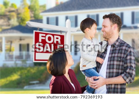 Young Mixed Race Caucasian and Chinese Family In Front of For Sale Real Estate Sign and House.