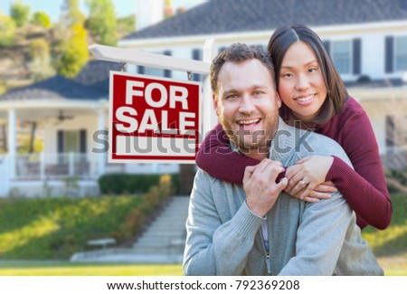 Mixed Race Caucasian and Chinese Couple In Front of For Sale Real Estate Sign and House.