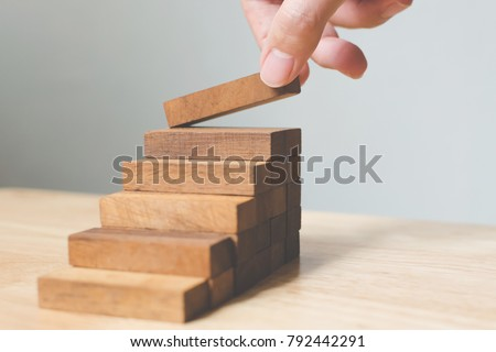 Hand arranging wood block stacking as step stair. Ladder career path concept for business growth success process, Copy space #792442291