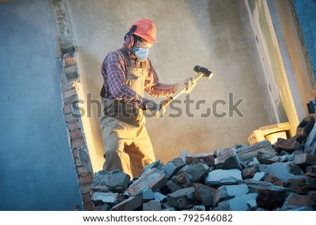 worker with sledgehammer at indoor wall destroying Royalty-Free Stock Photo #792546082