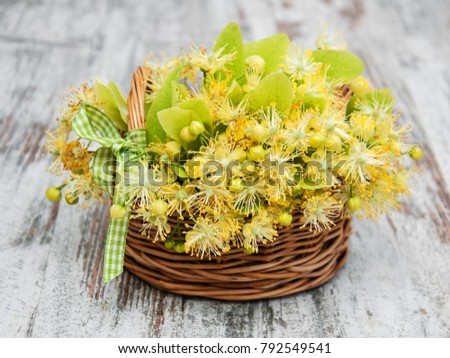 Basket  with linden flowers on a old wooden table #792549541