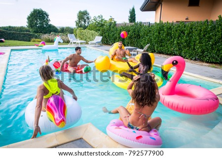 Multiracial group of friends having party in a private villa with swimming pool - Happy young people chilling with shaped air mattresses #792577900