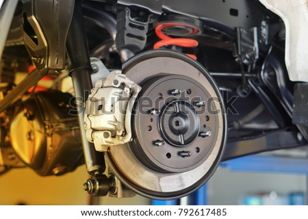 Disc brake of the vehicle for repair, in process of new tire replacement. Car brake repairing in garage.Close up. Royalty-Free Stock Photo #792617485