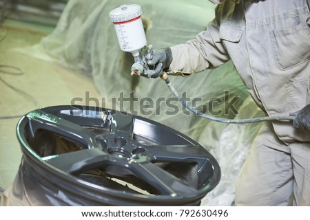 Automobile disc restoring. Painter painting light alloy wheel with spray Royalty-Free Stock Photo #792630496