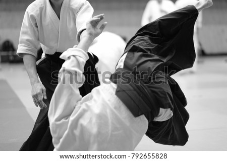 The participants of the training in special clothes of aikido hakama work out the methods of single combat