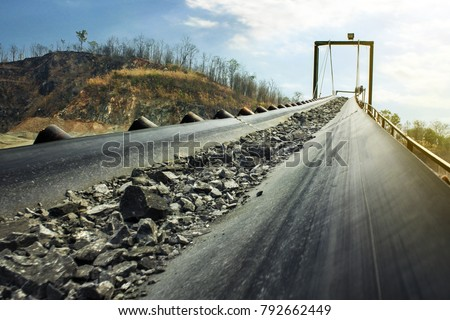 Industrial belt conveyor moving raw materials from mine Royalty-Free Stock Photo #792662449