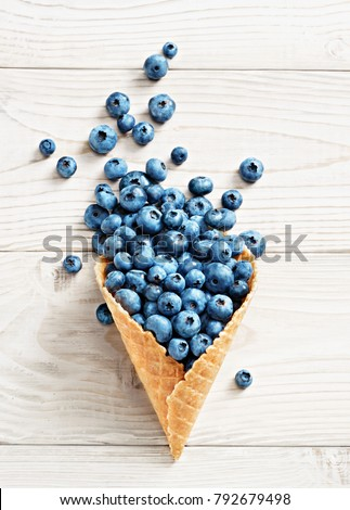 Blueberry explosion. Photo of blueberry in waffle cone on white wooden table. Top view. High resolution product.