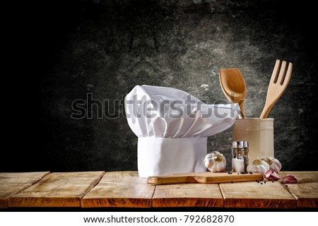 Cook hat and wooden table of free space  Royalty-Free Stock Photo #792682870