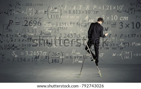 A businessman in elegant suit standing on a small ladder and writing numbers, calculating on grey wall background #792743026