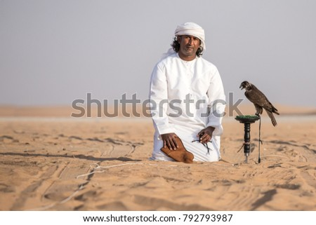 Abu Dhabi, UAE - Dec 15, 2017: Man in a traditional emirati dress proudly posing with his trained show falcon. #792793987