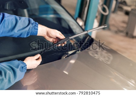 Technician is changing windscreen wipers on a car station. Royalty-Free Stock Photo #792810475