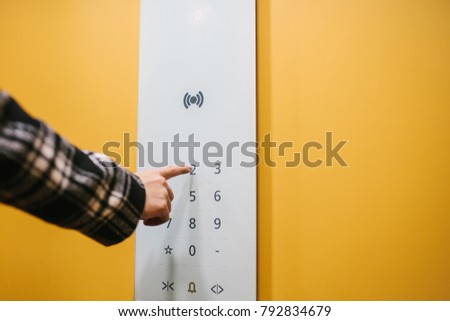 A woman clicks on an electronic button in a modern elevator. Inside the elevator.