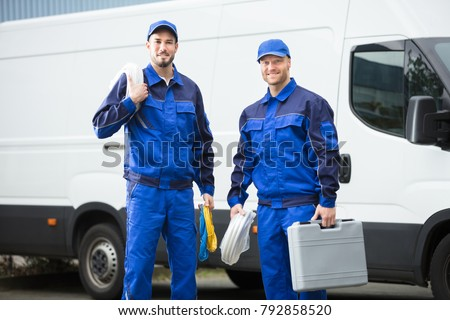 Smiling Repairman With Toolbox And Cable Standing In Front Of Vehicle #792858520
