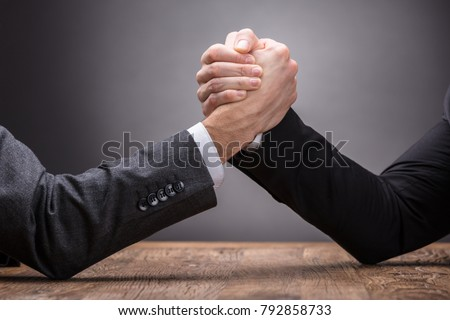 Close-up Of Two Businesspeople Competing In Arm Wrestling On Grey Background