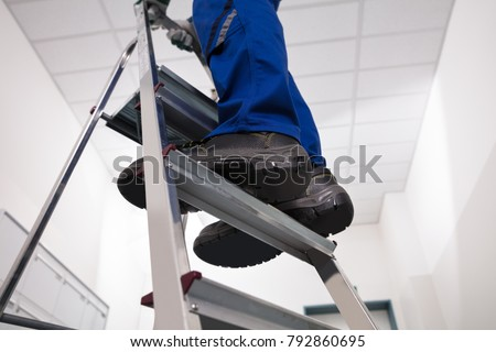 Close-up Of Man Standing On Steel Ladder #792860695