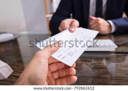 Close-up Of A Businessperson's Hand Giving Cheque To Colleague At Workplace Royalty-Free Stock Photo #792862612