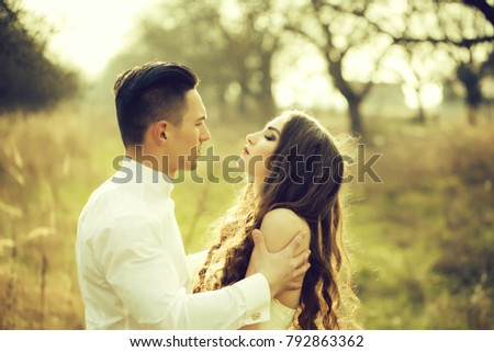Young happy wedding couple of pretty woman and man undressing in field outdoor #792863362
