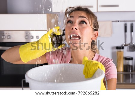 Shocked Woman Calling Plumber While Collecting Water Leaking From Ceiling Using Utensil Royalty-Free Stock Photo #792865282