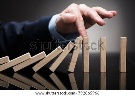 Close-up Of A Businessperson Stopping Wooden Blocks With His Finger From Falling On Desk #792865966