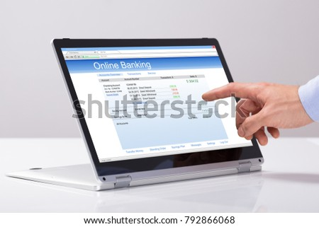 Close-up Of Male's Hand Using Online Banking On Hybrid Laptop Over The White Desk #792866068